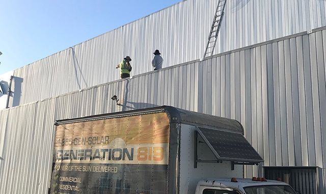 workers on commercial building with truck parking in front