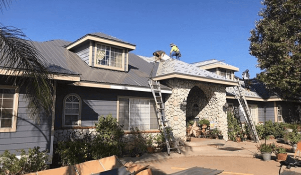 workers on house installing metal roof